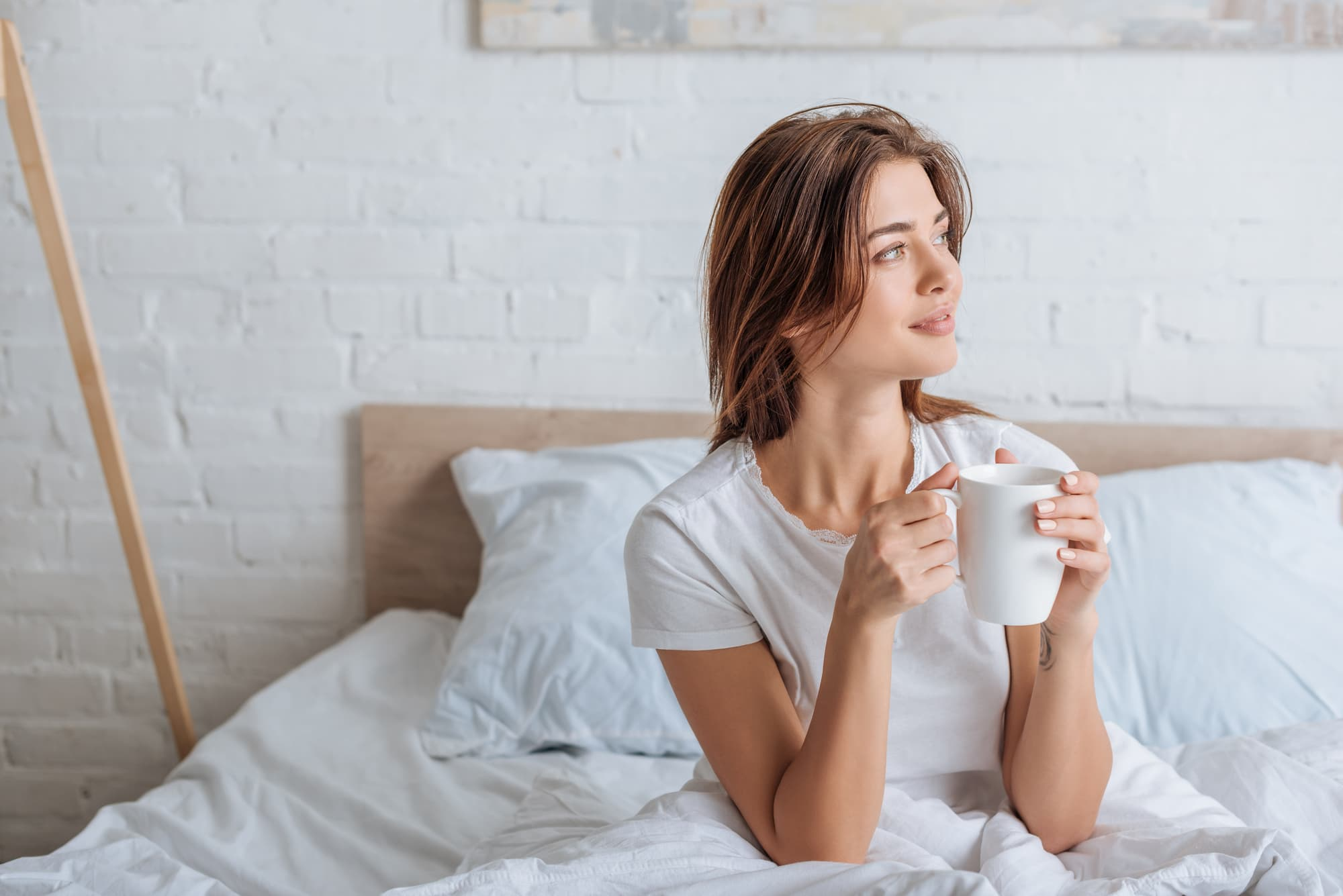 Happy young woman holding cup with tea in be